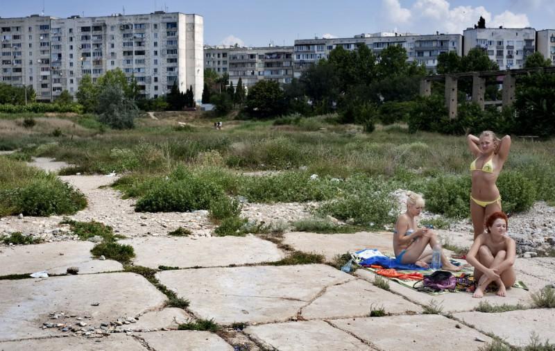 Местные девушки загорают на берегу одной из бухт Севастополя, Крым.