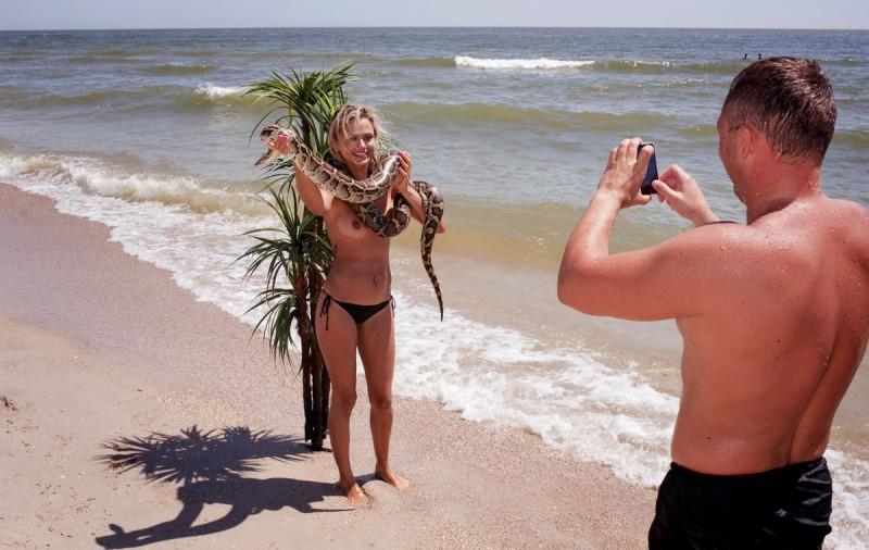 Девушка позирует на фоне пластиковой пальмы с арендованной змеей в руках. Затока, Одесская область,