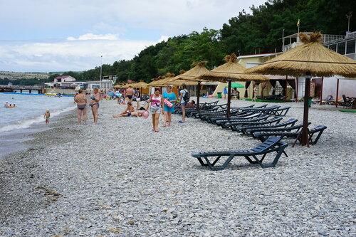 Геленджик. Галечный пляж с зонтиками и лежаками.