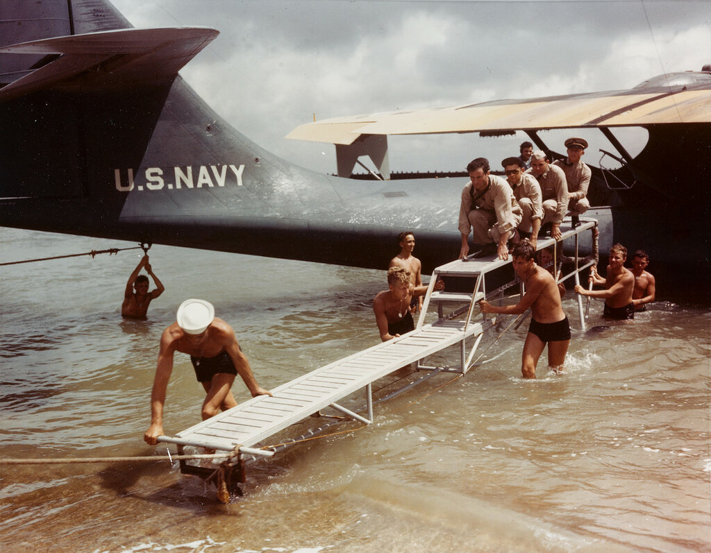 Consolidated PBY-3 CATALINA Patrol Plane (BU# 0844). Flight crew is carried ashore on a boarding dock, at a Naval Air Station Waterfront, circa 1940-42.
