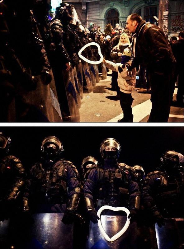 5. Румынский ребенок вручает воздушный шарик работнику полиции во время протестов в Бухаресте.