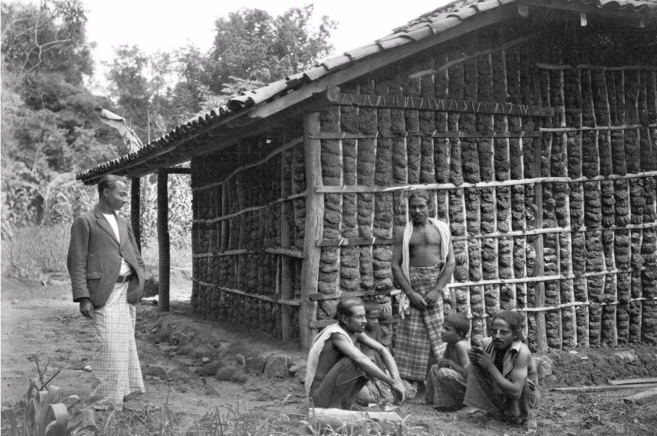 47. Мужчины с ребенком возле дома в Медагаме
