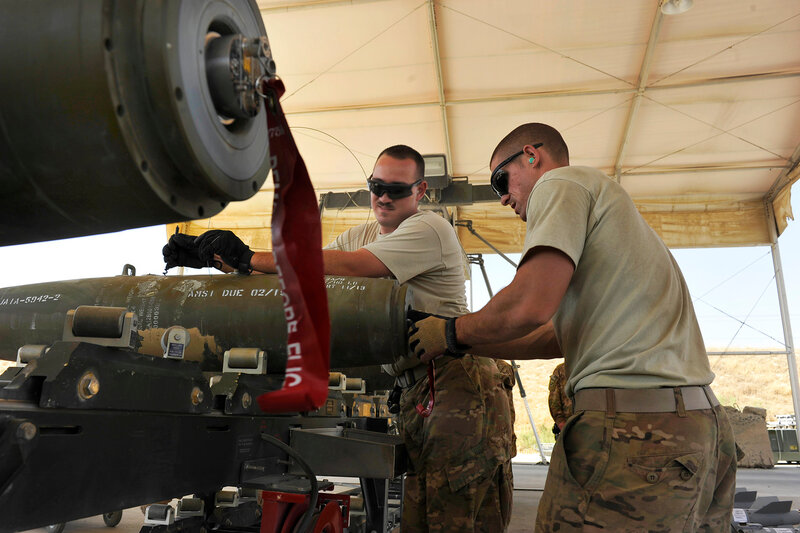 BAGRAM AIRFIELD, Afghanistan -- U.S. Air Force Senior Airman Christopher Reed (left) and Airman 1st Class Mark Mayeaux, munitions systems Airmen with the 455th Expeditionary Maintenance Squadron, install the power cable that connects the initiator to the
