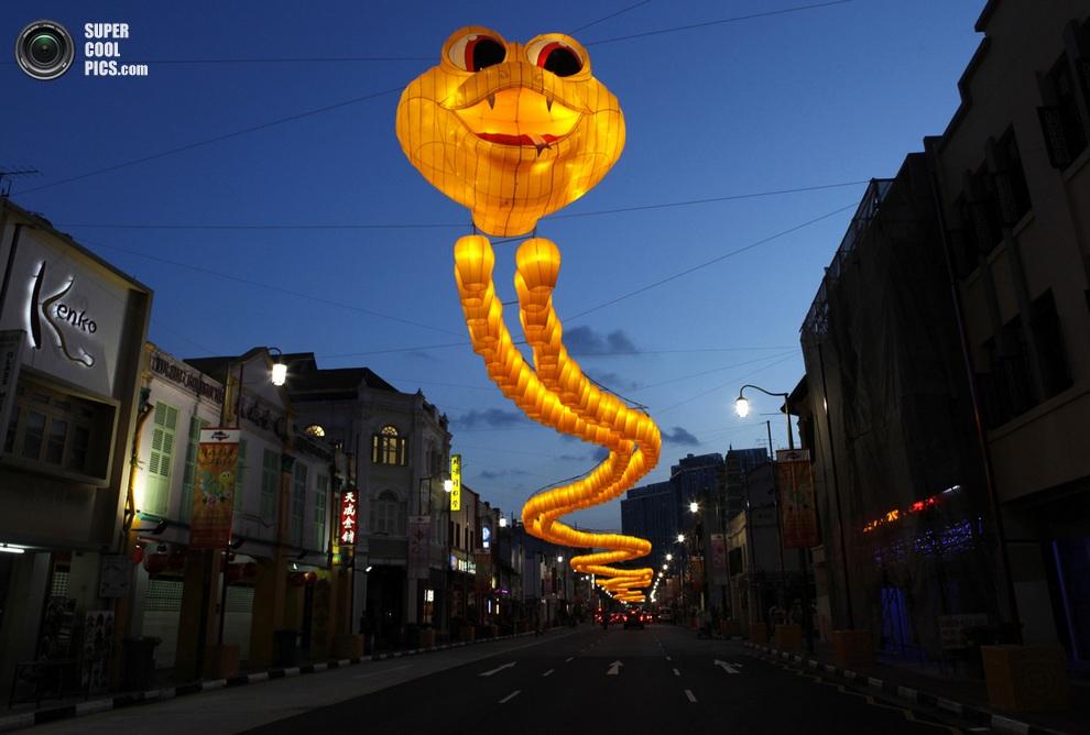 Огромная змея из желтых небесных фонариков украшает улицу,Сингапур.(REUTERS/May Naji)