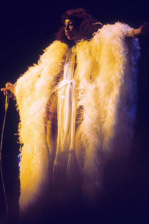 Королева диско Донна Саммер выступает на сцене в костюме из перьев, около 1976 года.