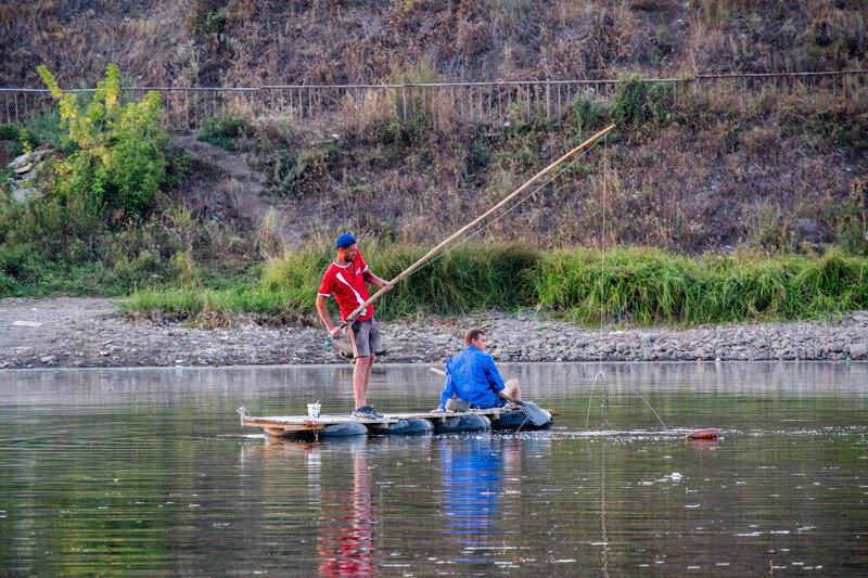 мужчина на лодке вытягивает снасть из воды