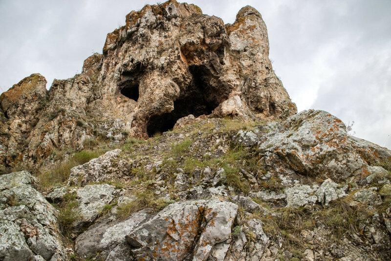 Пещеры в скале на фоне серого неба