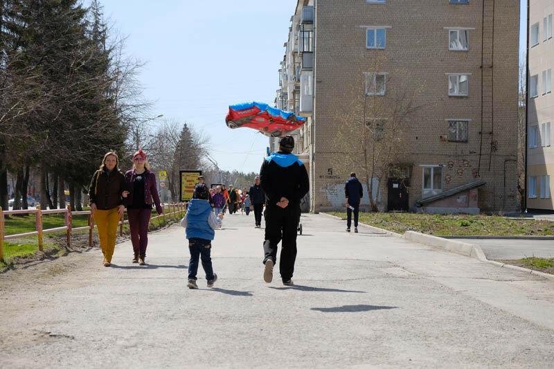 мальчик и дедушка идут по улице с воздушным шаром
