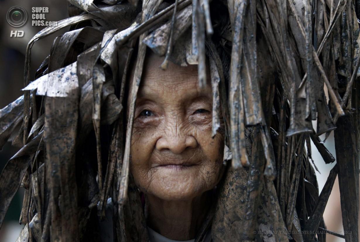 Филиппины. Алиага, Нуэва-Эсиха. 24 июня. Филиппинская католичка, покрытая грязью и одетая в сухи