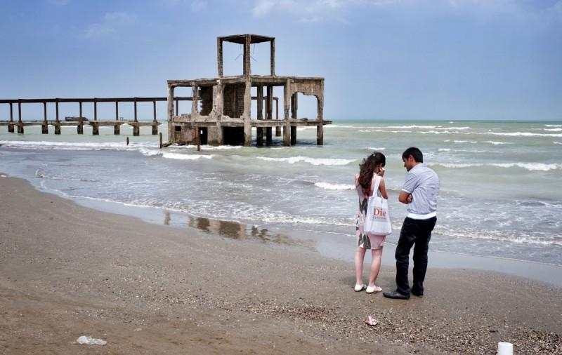 Пара спорит на берегу, на фоне — заброшенный советский ресторан. Сумгаит, Азербайджан.