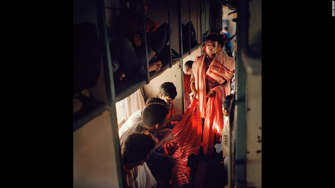 Торговец предлагает текстильные изделия пассажирам поезда «Вивек Экспресс», следующего по самому про