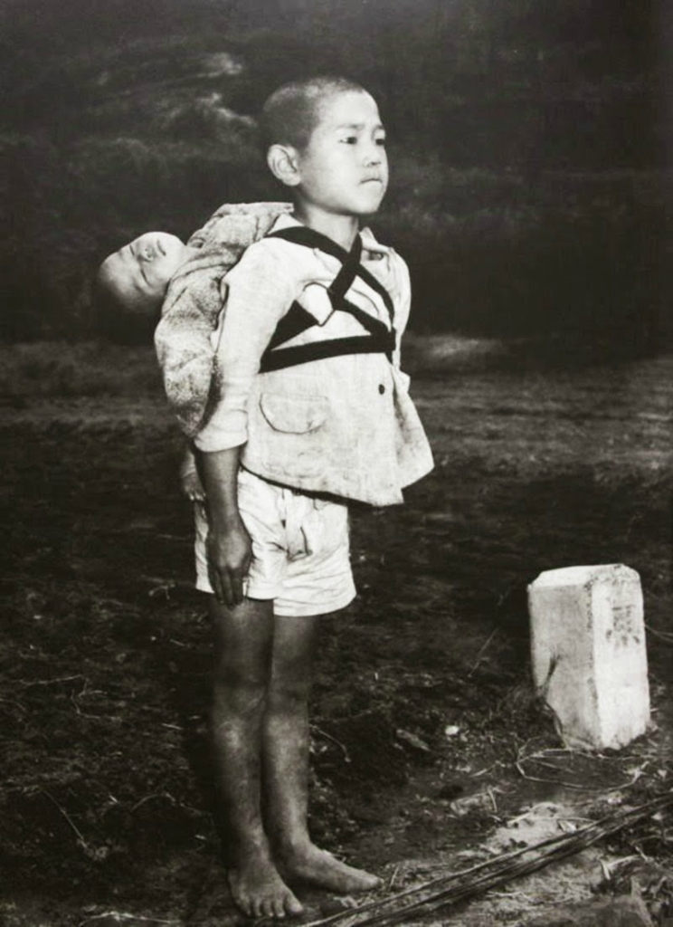 A-Japanese-boy-standing-at-attention-after-having-brought-his-dead-younger-brother-to-a-cremation-pyre-1945.jpg