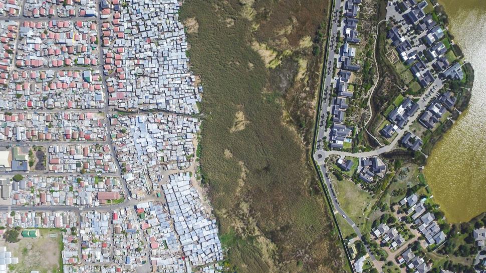 В годы апартеида чернокожих людей насильно выгоняли из их домов в сельской местности и загоняли в тр