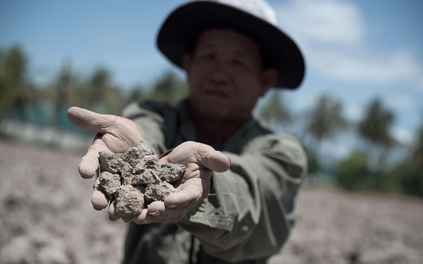 7. Там где раньше зеленели посевы, сегодня пересохшая почва, которую демонстрирует тайский фермер.