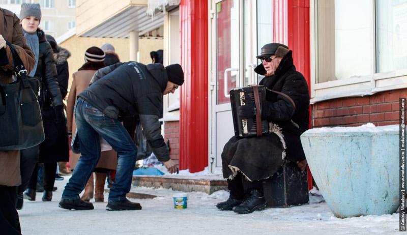 играющий баянист зимой на улице