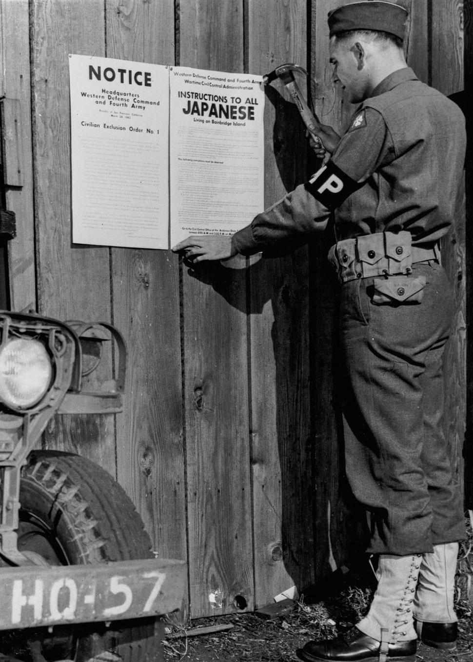Сотрудник военной полиции вывешивает указ о лишении прав группы граждан номер 1, который требует эва