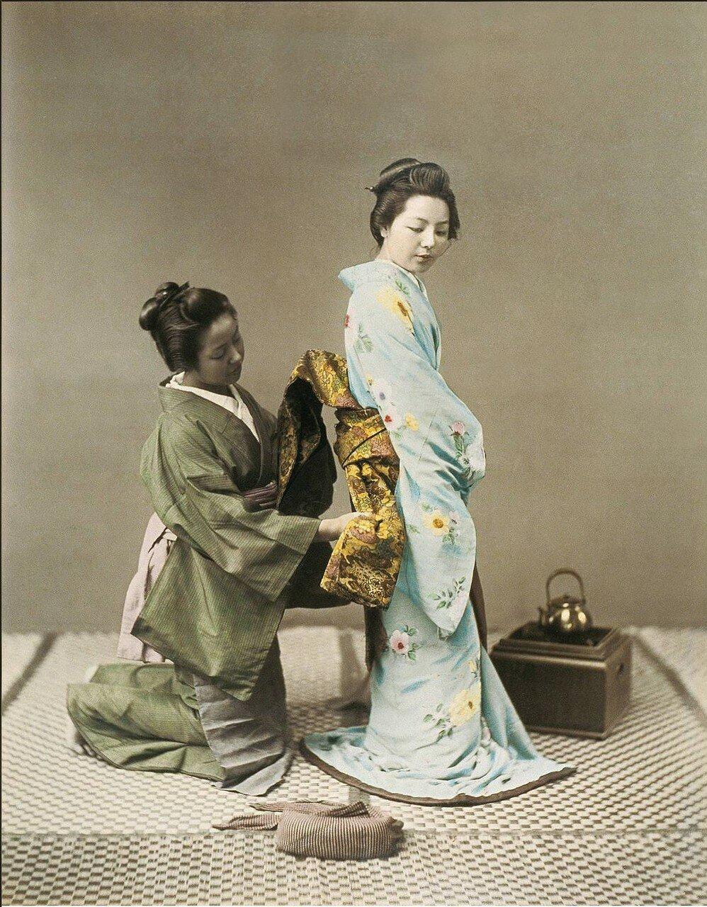 Служанка завязывает оби для гейши