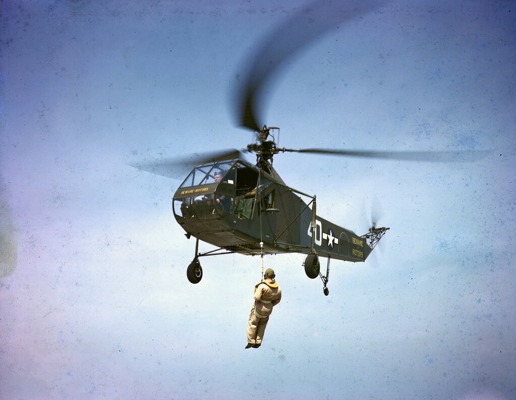 U. S. Coast Guard Sikorsky R-4B (BuNo 39040, sn 43-46525) in flight, hoisting a man in a sling.