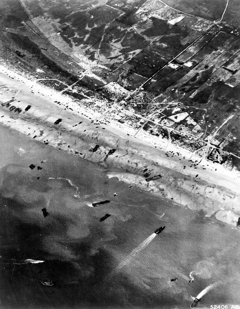 D-Day beach traffic, photographed from a Ninth Air Force bomber on 6 June 1944. Note vehicle lanes leading away from the landing areas, and landing craft left aground by the tide.