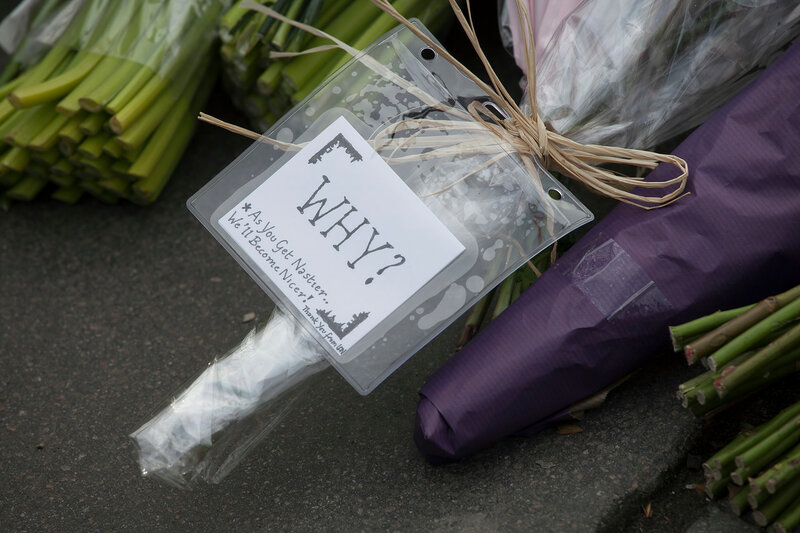 Flower tributes are left on the pavement on the edge of a police cordon near to parliament in London,