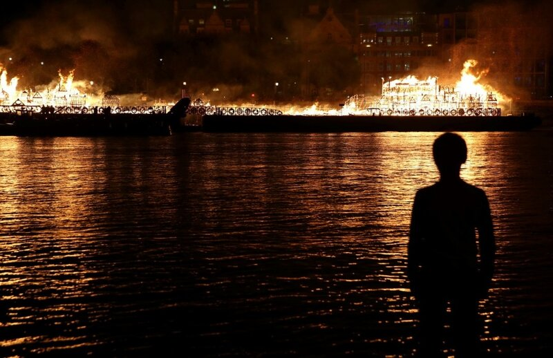 A boy watches as a 120-meter long model of the 17th century London skyline is set alight on the River Thames to commemorate the 1666 Great Fire of London in London