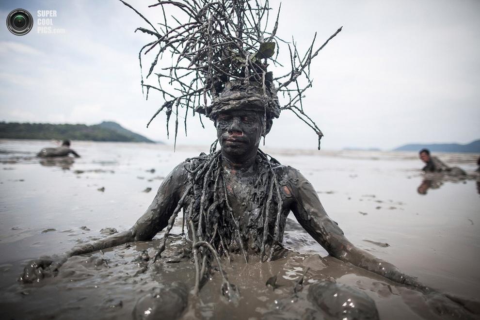 Парень с кустом на голове медитирует в грязи. (Victor MORIYAMA/AFP/Getty Images)