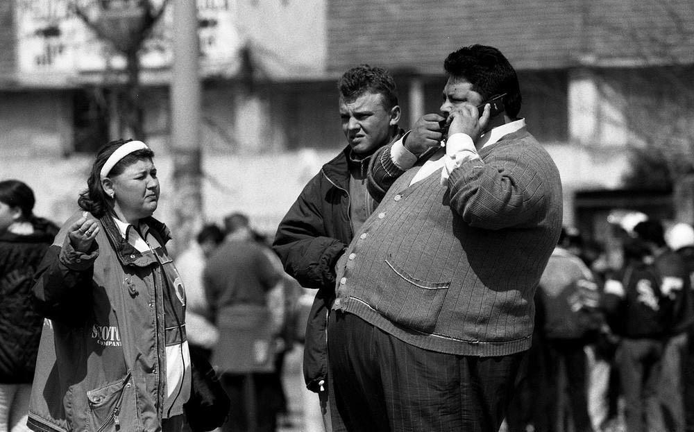 Футбольные фанаты едят семечки и болтают по телефону в ожидании игры у стадиона «Рапид» в Бухаресте.