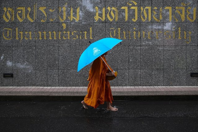 A buddhist monk walks after collecting alms during the 40th anniversary of a campus massacre by stat