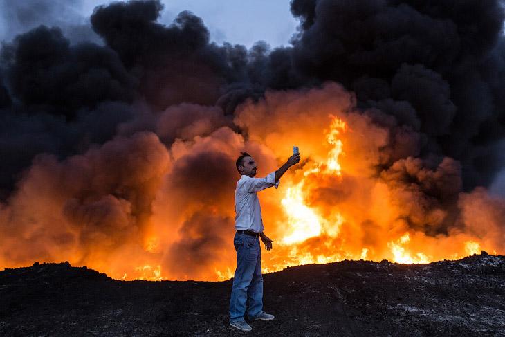 1. Это пригород Мосула Qayyarah. Повсюду виден огонь и дым от горящей нефти. (Фото Chris McGrat