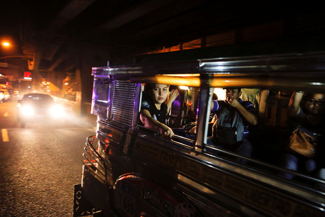 Passengers look from inside a passing jeepney at the site where a man was killed in a shootout with