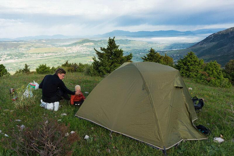 папа и ребенок (1 год) завтракают у палатки в Греции