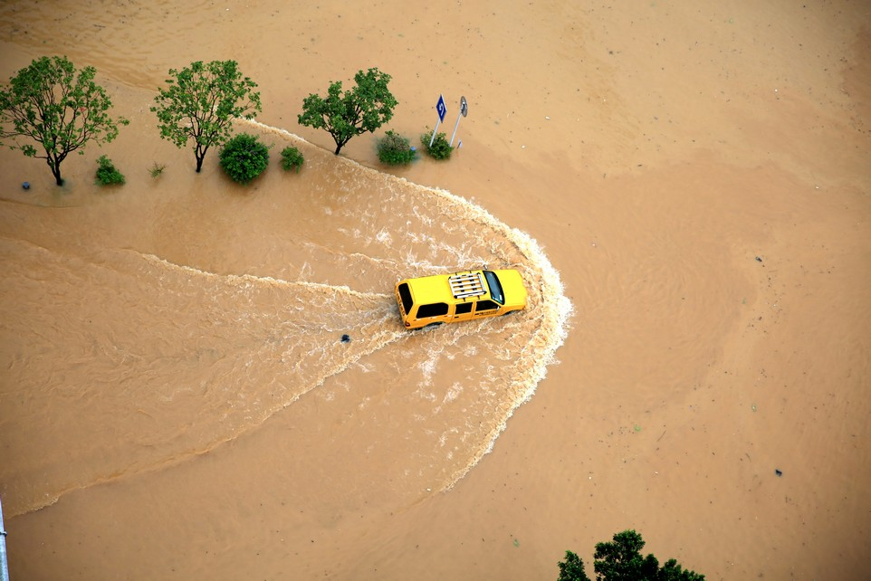 An automobile is seen passing a flooded street in Rongjiang