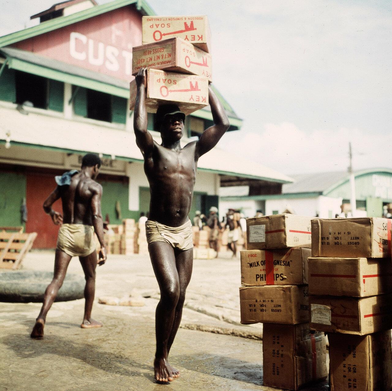 Носильщик переносит коробки из прибойных шлюпок на склад