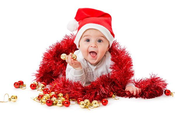 Малыш в шапке санты клауса с новогодней мишурой и шариками