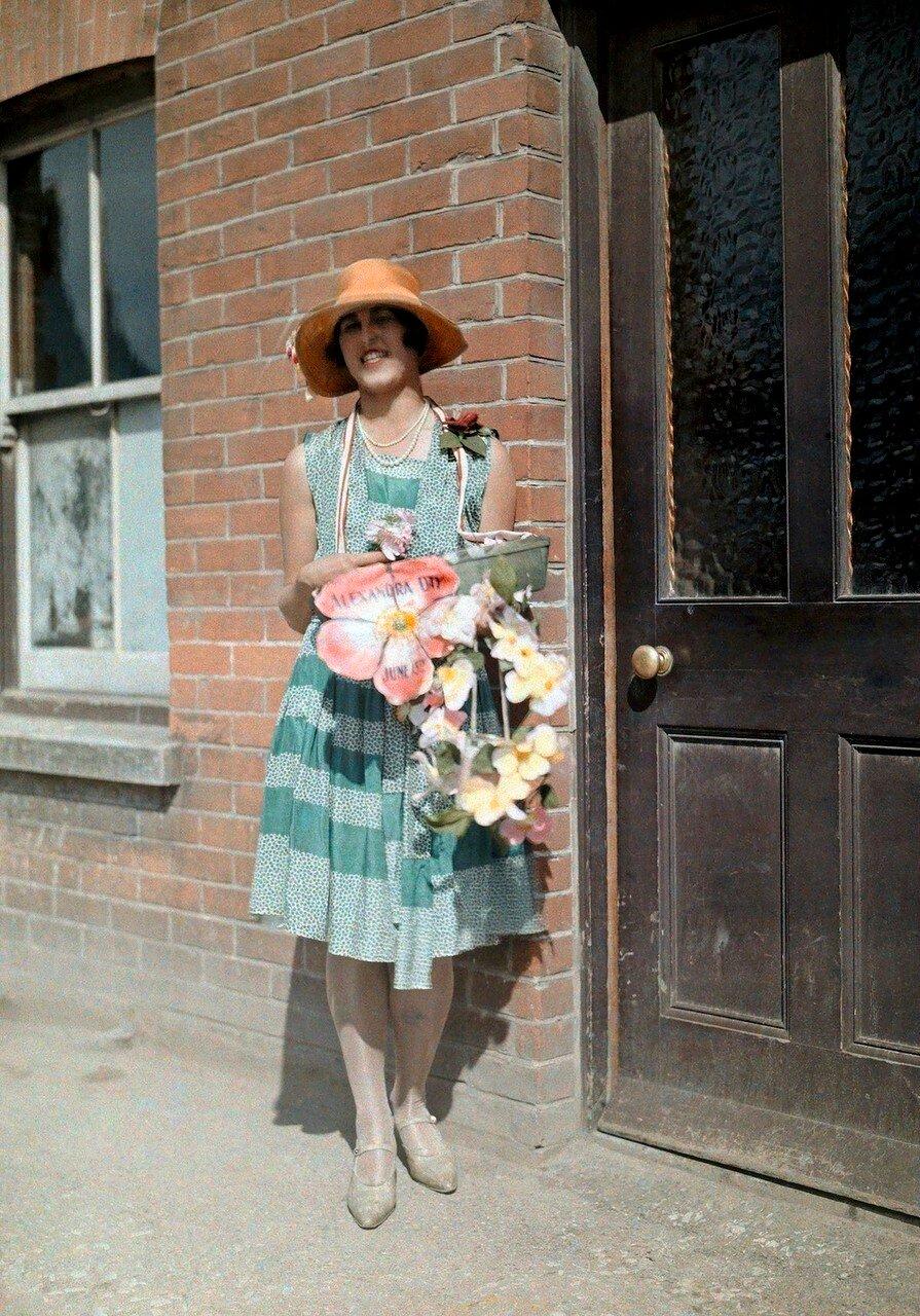 Молодая девушка продаёт искусственные цветы для благотворительной акции в День Александры в графстве Кент
