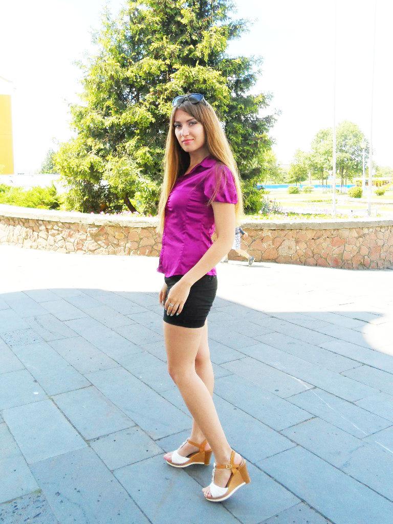 Веселая девушка в сиреневой блузке и шортах