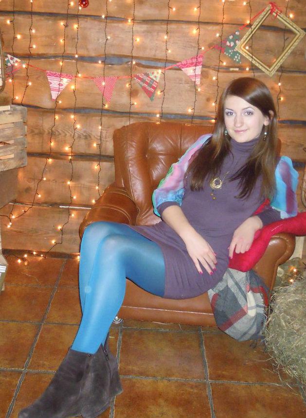 Красотка  в тунике и колготках на кожаном диване