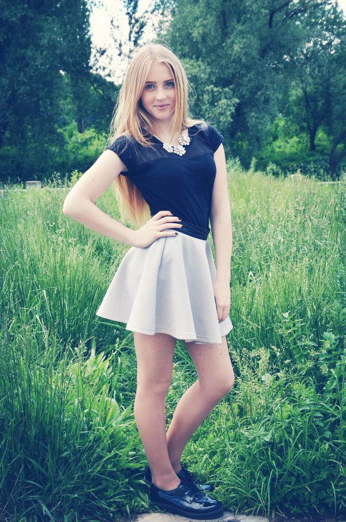 Юная блондинка в юбке на фоне травы