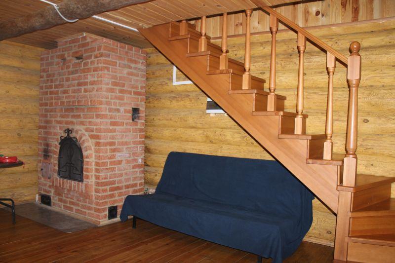 Первый этаж. Диван, который раскладывается. Камин и лестница на второй этаж. (09.06.2015)