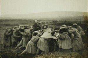 Австрийские пленные помогают вытащить автомобиль из грязи.