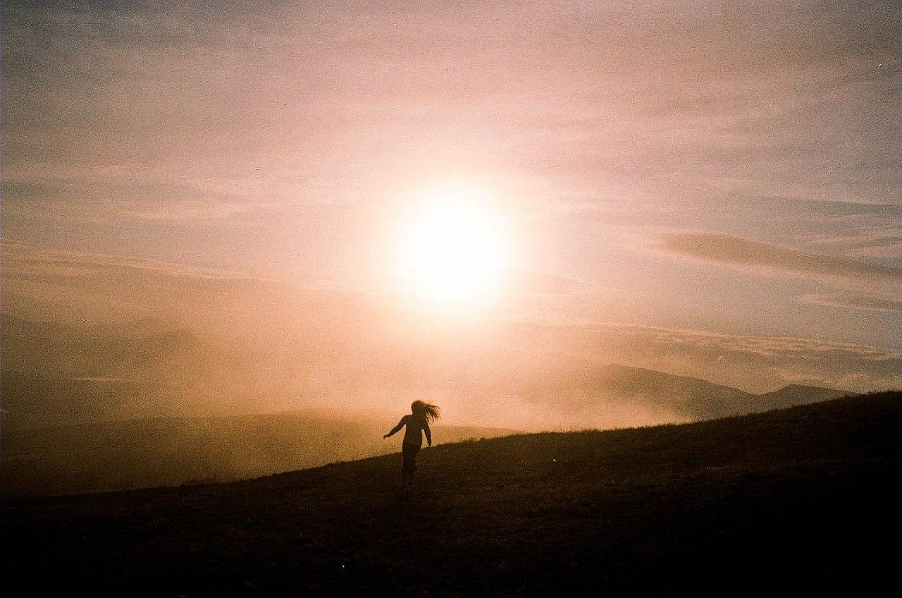 девушка на природе бежит на встречу солнцу
