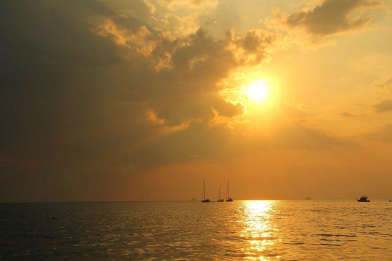 Закат в Андаманском море на пляже Ао Нанг (провинция Краби, Таиланд): солнечная дорожка, яхты, острова и волны