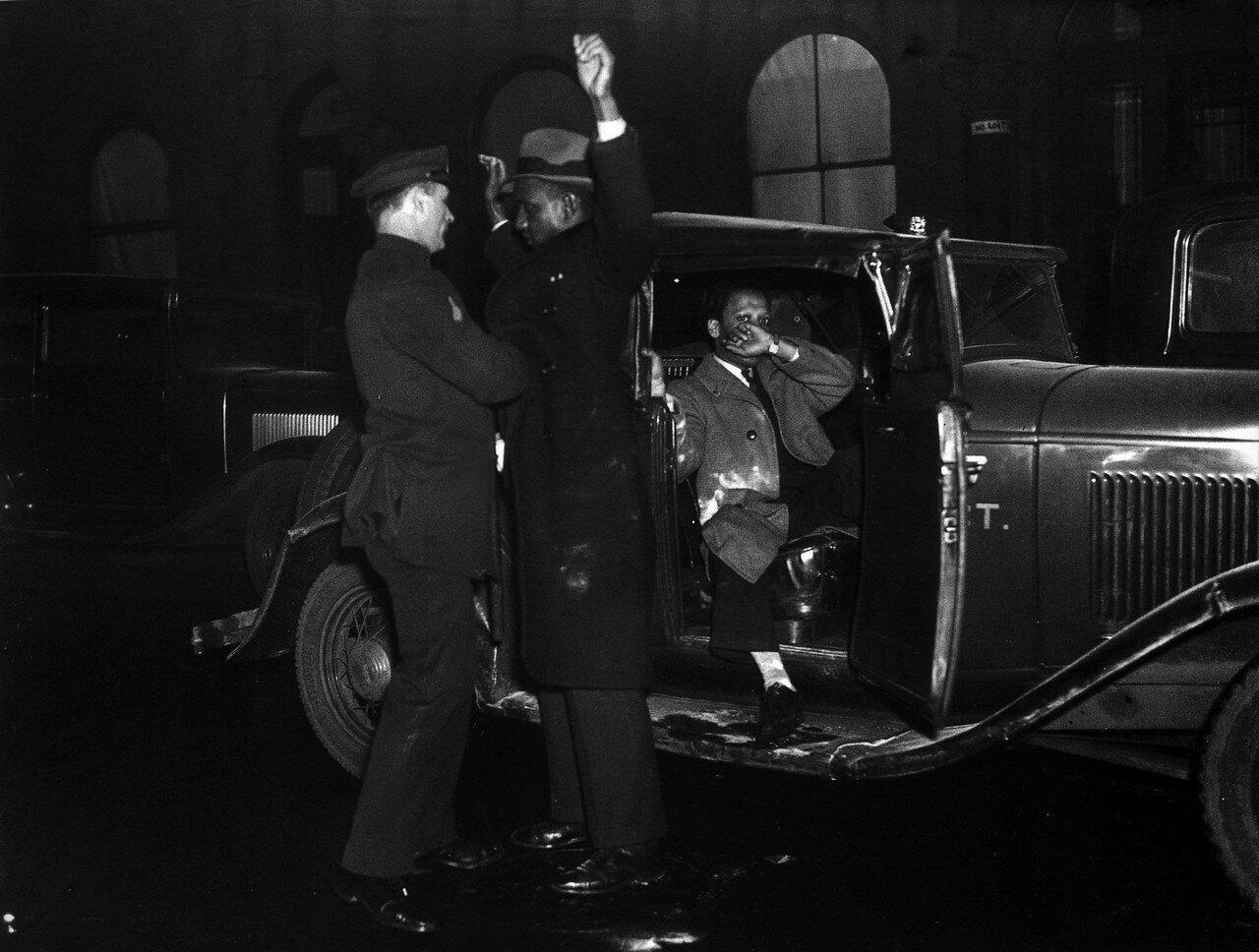 1935. 19 марта. Полиция досматривает негра во время черного бунта в Гарлеме