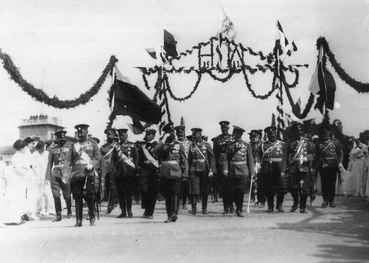 17. Императоры Николай II, Вильгельм II и сопровождающие офицеры проходят под триумфальной аркой, украшенной флагами и цветами в честь приезда Вильгельма II