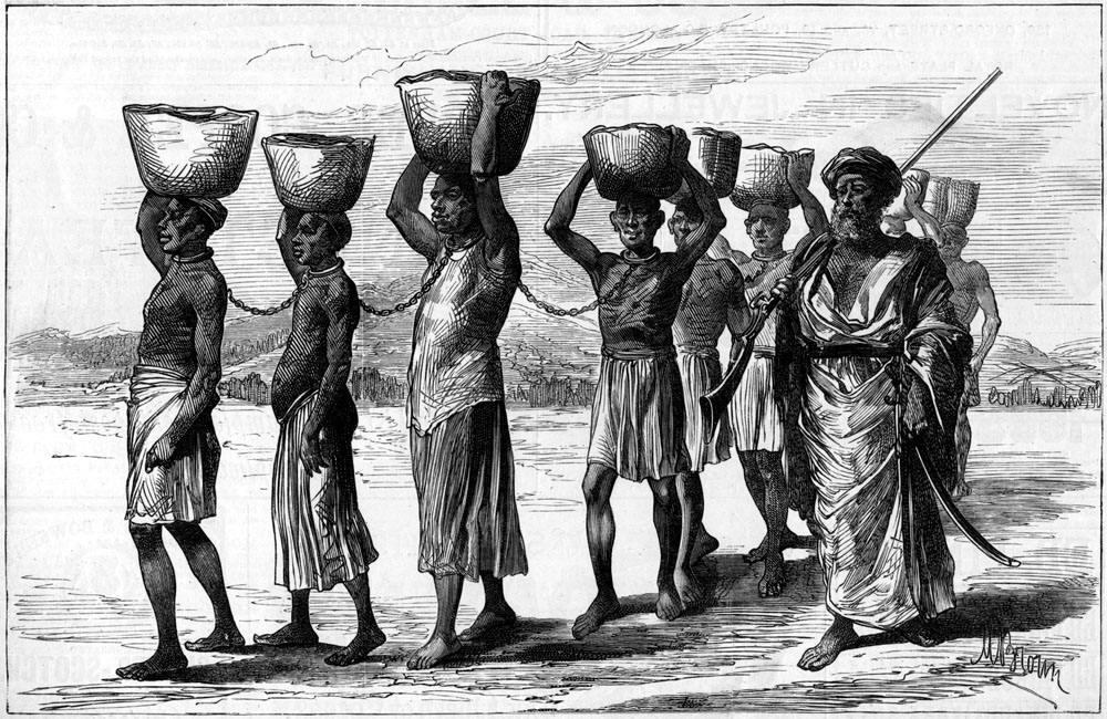 Колонна скованных между собой африканских рабов с грузом на головах под охраной пеших работорговцев (Восточная Африка, 1880-е годы)