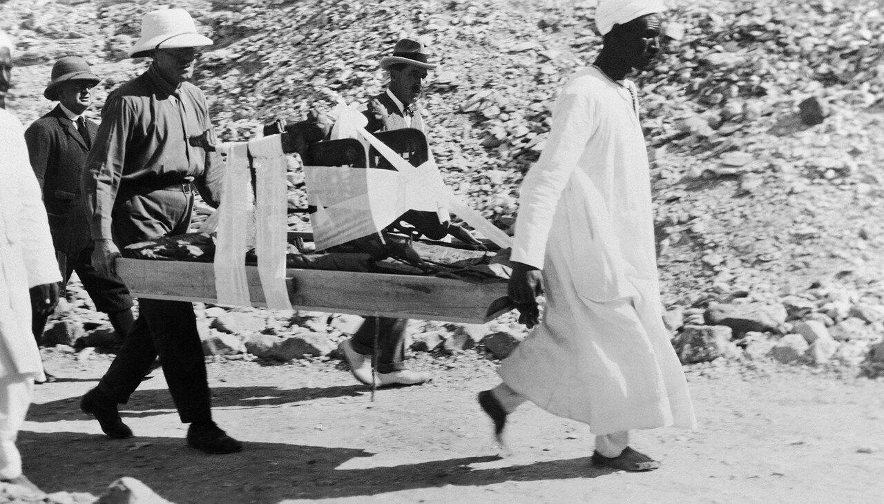 Говард Картер смотрит, как носильщики несут трон из гробницы Тутанхамона. 1923