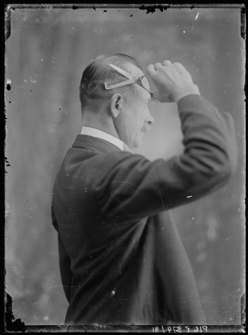 Man cutting his hair with scissors and comb, ca. 1915.jpg