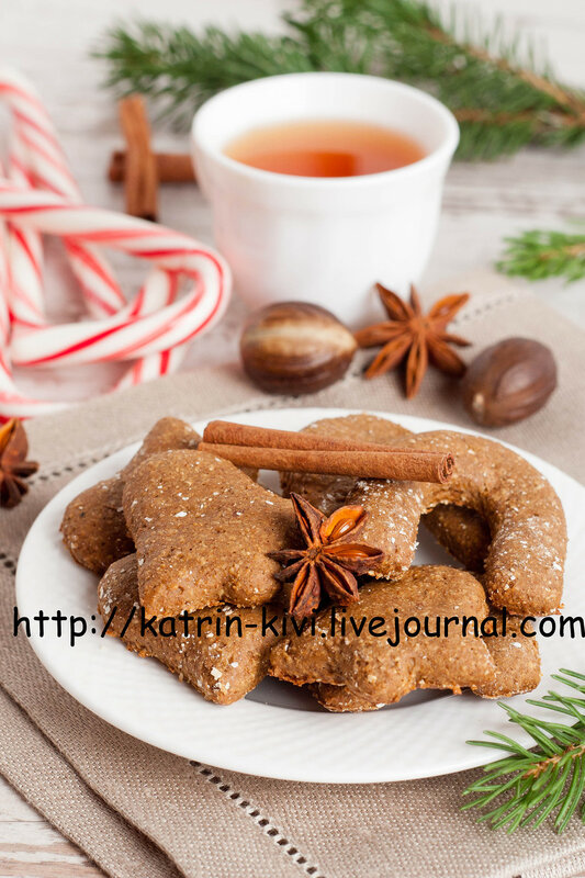 homemade gingerbread cookies on a plate, surrounded with spices, tea, caramel candy and christmas tree branch, close up