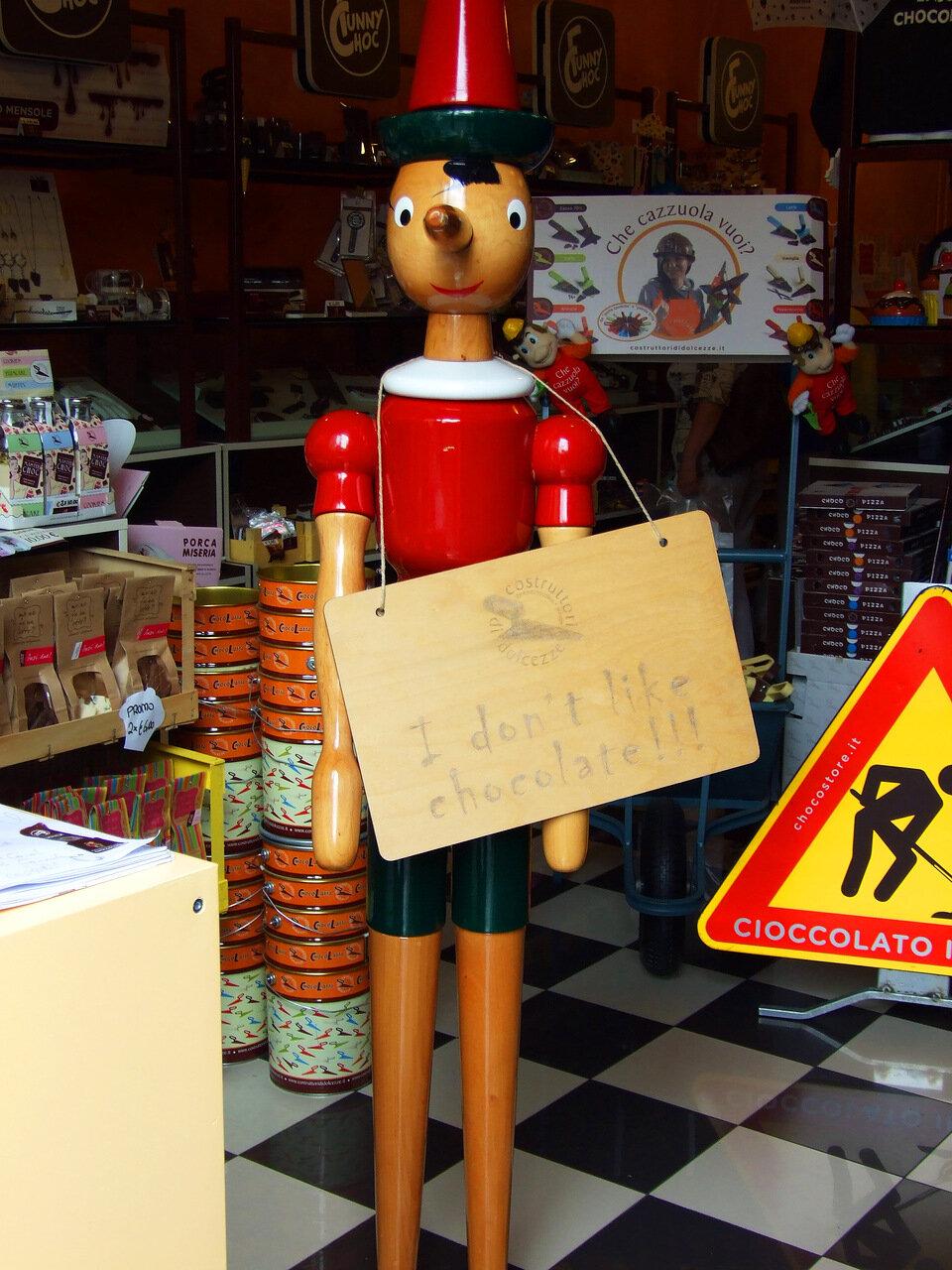 В магазине шоколада стоит Пиноккио с щитом на груди и забавной надписью I don`t like chokolate (Я не люблю шоколад)
