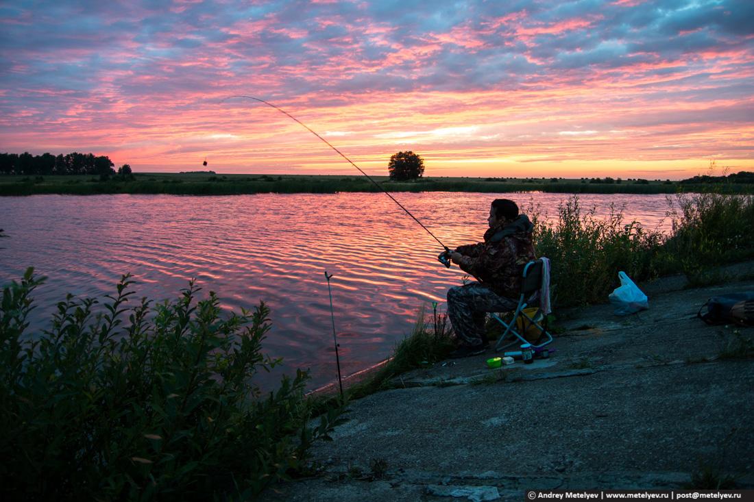 Рыбак на рассвете забрасывает фидер